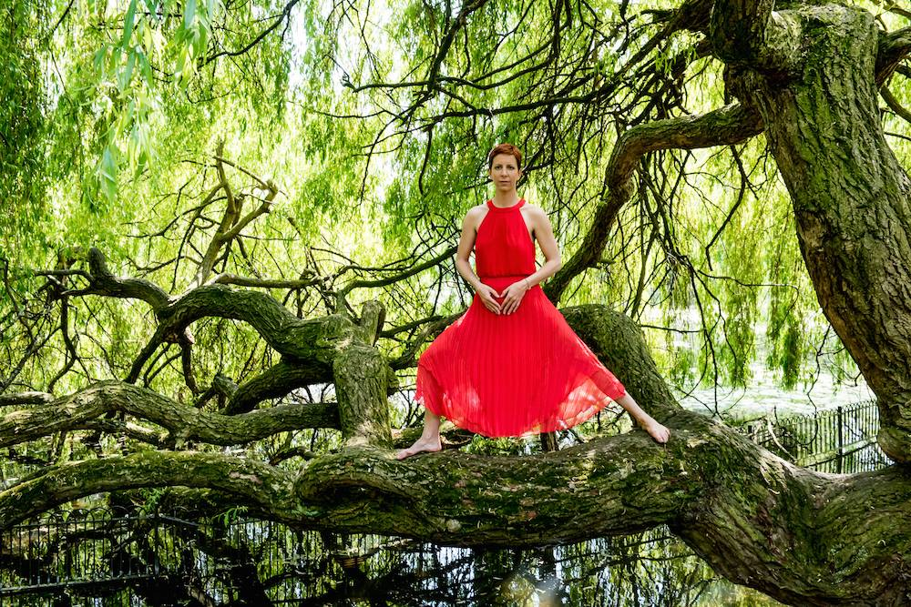 Katy Robinson Maha Yoga wearing red dress warrior tree pose asana on beautiful tree across water in Battersea Park May 2016 Emma Myrtle Photography